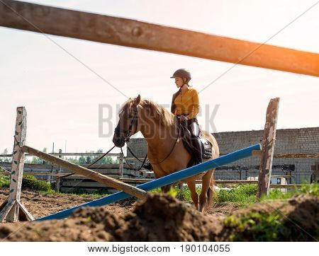 Young cheerful girl rides on a brown horse. Riding training. Horseback Riding.