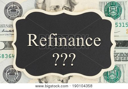 Refinance text and question marks on chalkboard on USA twenty dollar bills