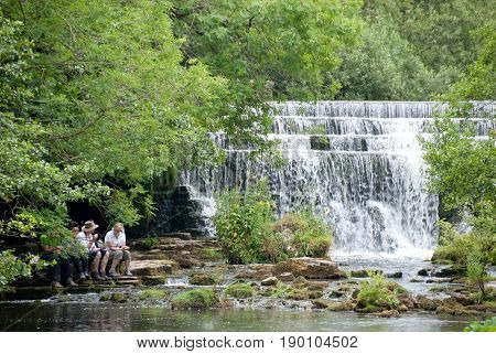 Derbyshire UK - July 20 2014 - Sitting beside the waterfall at Monsal Dale Weir on the River Wye Monsal Dale