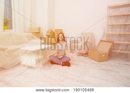 Young girl trying to keep calm and relax during the relocation. Female sitting on the floor with crossed legs and closed eyes relaxing while unpacking boxes.