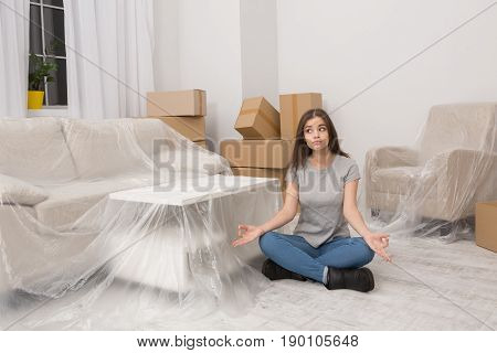 Woman in casual clothes sitting on the floor relaxing after unpacking thigs during the relocation. Young brunnete girl sitting with her legs crossed in yoga position.