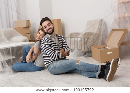 Young man and woman are tired after preparation for relocation. Couple sitting on the floor back to back relaxing after packing boxes for movin in new apartment.