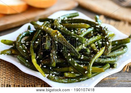 Fried garlic arrows appetizer. Spicy green garlic arrows with spices and sesame seeds on a plate. Easy, cheap and healthy recipe idea. Closeup