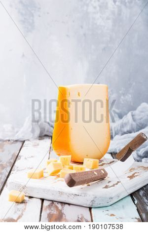 Delicious dutch gouda cheese with cheese cubes and special knife on oud wooden table. Copy space.