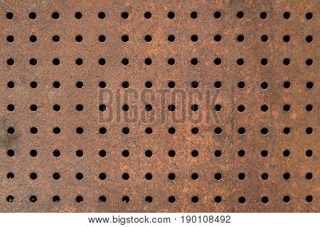 Rusty texture of perforated metal. Regular pattern of holes in a sheet of metal. Rusty iron background with holes