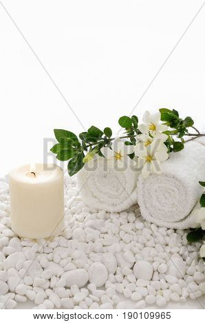 Beautiful white Gardenia laying with towel, candle on white stones background