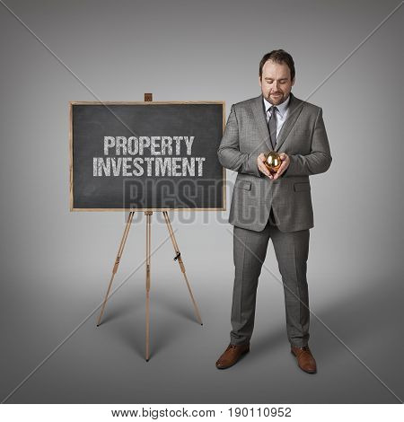 Property investment text on  blackboard with businessman and golden egg