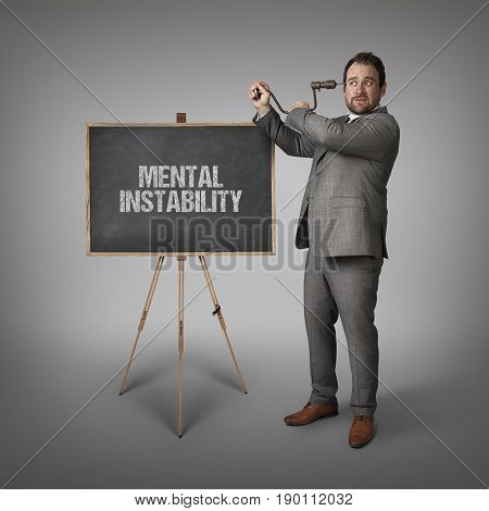 Mental instability text on blackboard with businessman drilling his head