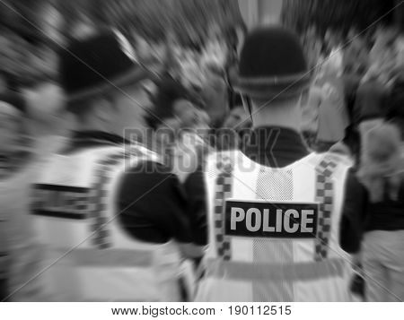 Zoom blur effect applied to two policemen overlooking crowd of people