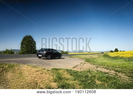 Ceske Stredohori Czech republic - May 19 2017: black car Opel Astra H stand by road between rape fields during spring afternoon