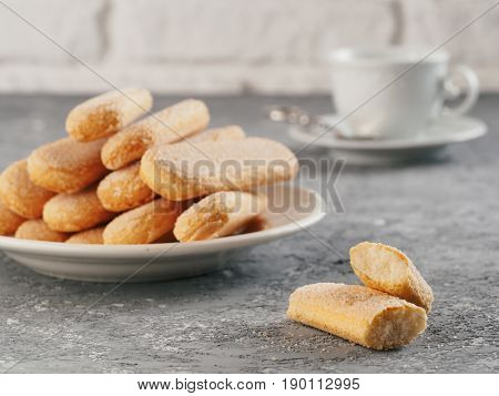 Italian cookie savoiardi and cup of coffee. Close up view of ladyfinger biscuit cookie on gray concrete background. Copy space.