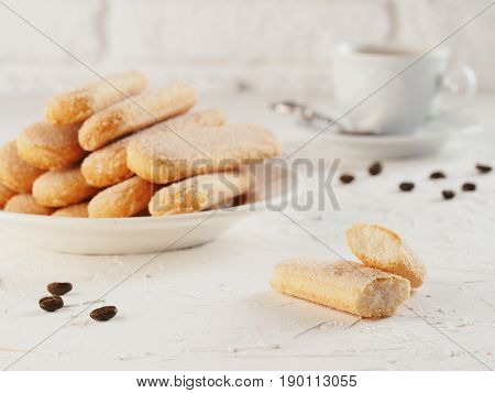 Italian cookie savoiardi and cup of coffee. Close up view of ladyfinger biscuit cookie on white concrete background. Copy space.