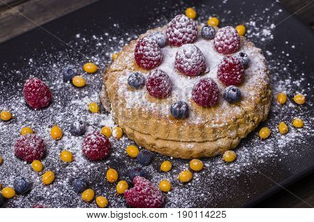 Cake with raspberries blueberries sea buckthorn sprinkled with powdered sugar on a black plate close up