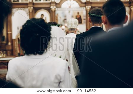 Back View Of Bride And Groom And Guests Priest In Church During Wedding Ceremony