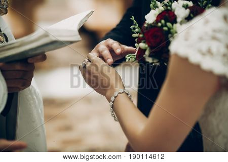 Bride And Groom Exchanging Wedding Rings, Putting On Fingers During Wedding Ceremony In Church. Wedd