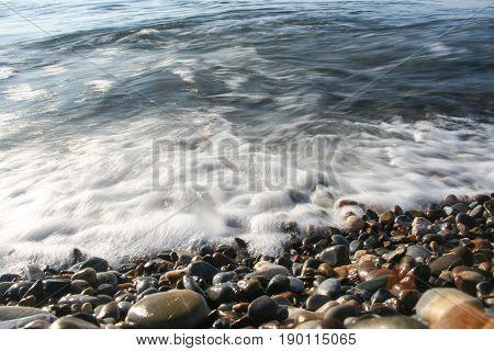 Sea Shock Wave Foam On The Pebble Stone Beach