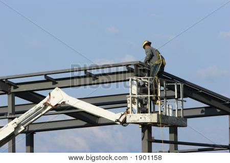 Construction worker on a cherry picker crane erecting a building at a site. poster