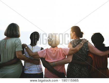 Group of senior women friends arm around on the beach