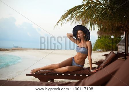 Young woman relaxing in a deck chair on a tropical beach at sunrise or sunset, girl on a beach sun bed chilling near ocean and palms on Maldives