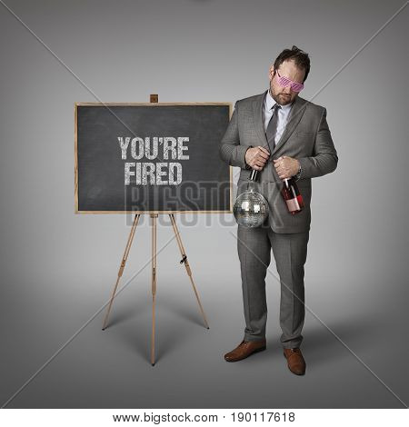 Youre fired text on blackboard with businessman and key