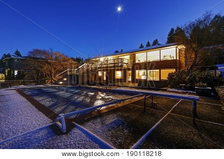Sunset View Of Two Story Home With Snow Covered Pool