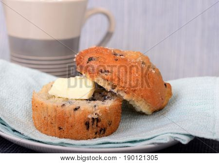 Delicious warm blueberry muffin served with butter and a cup of coffee