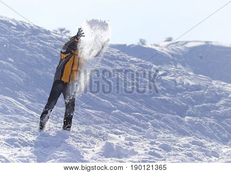 man throws snow in the winter . A photo