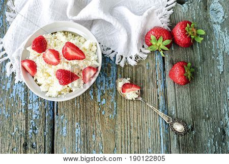 Plate with cottage cheese and strawberries on a wooden table, top view