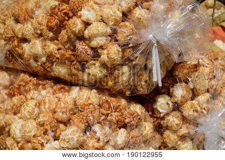 Spicy caramel covered kettle corn popcorn in large bags at farmer's market