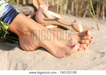 Tidy tanned sexual soft woman feet on the beach sand. Summertime outdoors close-up.