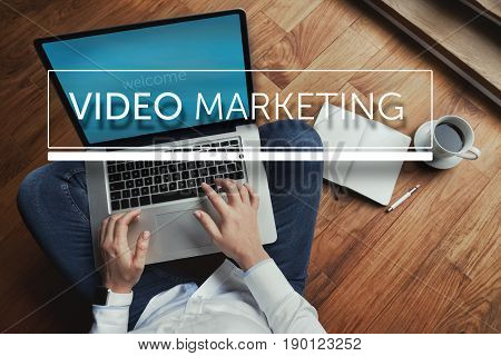 Top view of young woman sitting on the wooden floor with laptop and coffee with video marketing inscription in the foreground