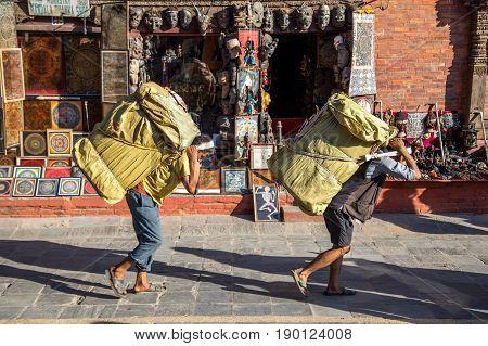 Kathmandu, Nepal - October 19, 2014: Two nepalese men carrying heavy packages on their backs