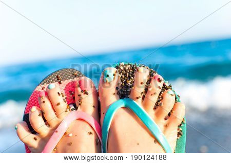 Funny woman feet with multi-colored pedicure in slippers on summer pebble beach background. Inspirational vibrant outdoors horizontal close-up image.