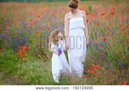 Mom and child walking holding hands outdoors. Two women in dresses Mother and the daughter hold hands.