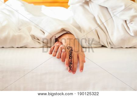 Sleeping little child hands with tattoo on white bed linen. Indoors closeup.