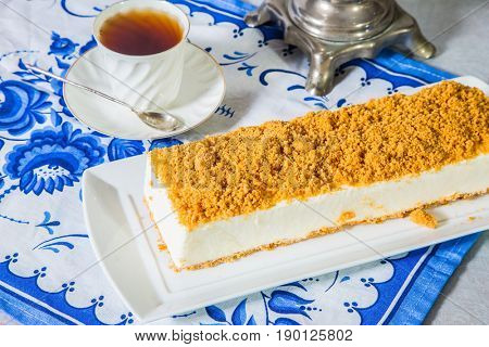 Professional bakery. Exquisite white cheesecake, sprinkled with sweet orange crumbs. The background is samovar and porcelain white cup with hot tea on blue kitchen towel