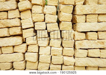 Rock limestone stone brick tile wall aged texture detailed pattern background. ancient rustic limestone pattern