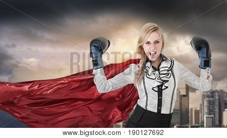 Young woman won battle. Portrait of businesswoman in formal wear with super hero cape