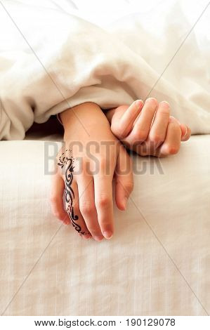 Little sleeping child hands with tattoo on white bed linen. Indoors closeup.