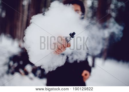 vaping man holding a mod device. cloud of vapor. Vape