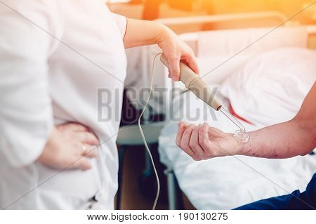 doctor with the phone treats a patient with a skin disease using the Darsonval apparatus for the treatment of dermatitis, apathic, seborrhea, eczema.