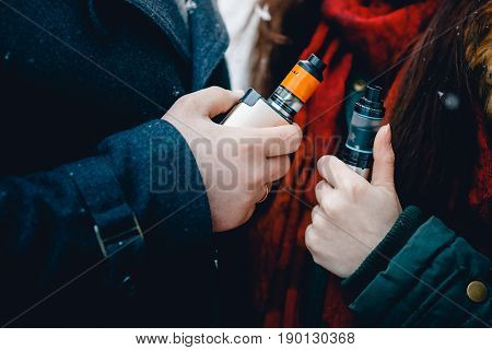 Close-up of a man and a girl are smoking electronic cigarettes wape mod and drip. There are clubs of steam. Concept of smoking in public places is steam and smoke.