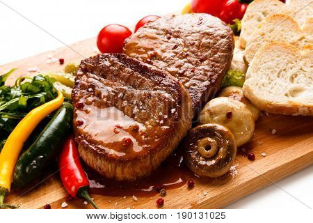 Grilled beefsteak with toasts on wooden board on white background
