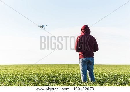 quadcopter summer outdoors, aerial imagery and recreation concept - male in jeans and fleece hoodie controls flight of superb white high-tech drone at low altitude, blue sky and field of green grass.