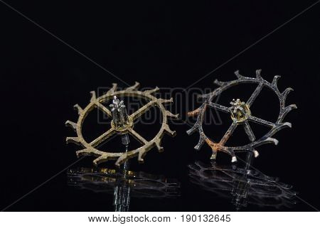 Watch Parts: Worn and Rusty Escape Wheels on Black Background