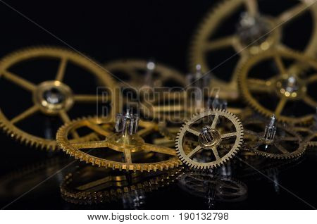 Watch Parts: Collection of Vintage Metallic Watch Gears on a Black Surface