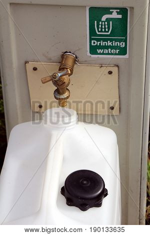 Filling A Drinking Water Container At A Campsite Water And Electricity Supply Point