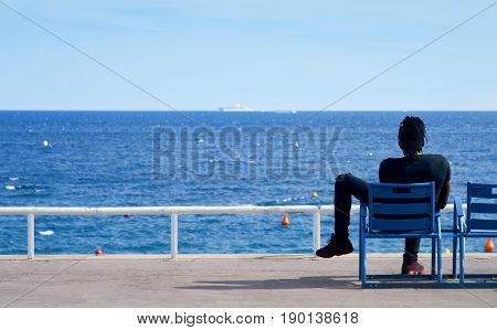 NICE, FRANCE - JUNE 4, 2017: Young man sitting in one of the characteristic blue chairs facing the Mediterranean sea at the famous Promenade des Anglais in Nice, in the French Riviera, France