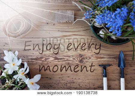 English Quote Enjoy Every Moment. Sunny Spring Flowers Like Grape Hyacinth And Crocus. Gardening Tools Like Rake And Shovel. Hemp Fabric Ribbon. Aged Wooden Background