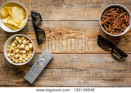watching TV set with chips and remote control on wooden background top view mock up